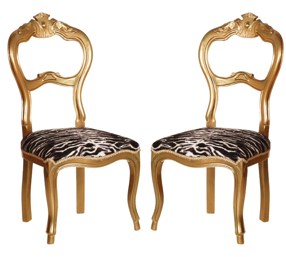 a pair of baroque golden chairs with zebra upholstery